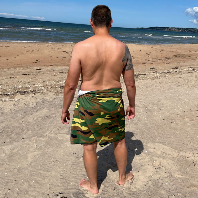 Towel Camouflage from TAC-UP GEAR wrapped around models waist on the beach and seen from the back
