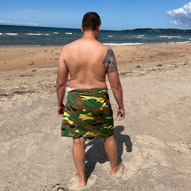 Towel Camouflage from TAC-UP GEAR wrapped around models waist on the beach and seen from the back at an angle