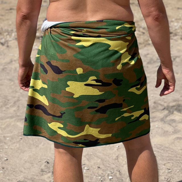 A close up look at the Towel Camouflage from TAC-UP GEAR wrapped around models waist on the beach and seen from the back