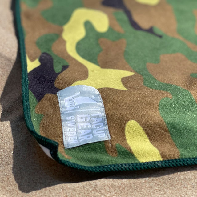 A close up on a Towel Camouflage from TAC-UP GEAR laying in the sun on the beach