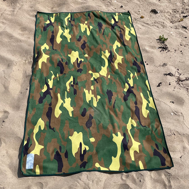 Towel Camouflage from TAC-UP GEAR lying flat on beach sand