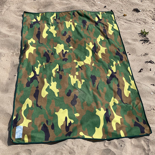 A Towel Camouflage from TAC-UP GEAR lying flat on beach sand