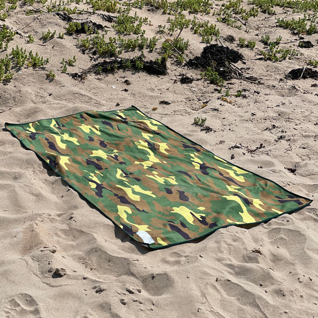 The Towel Camouflage from TAC-UP GEAR lying flat on beach sand and seen from an angle