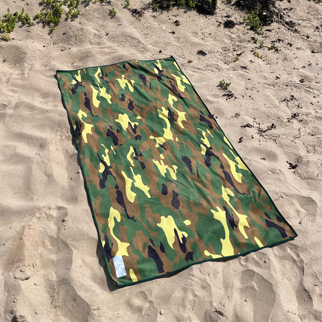 The Towel Camouflage from TAC-UP GEAR lying flat on beach sand