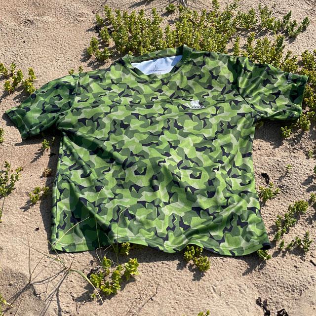 A Training T-Shirt M90 MI seen from a slight angle lying flat on the beach