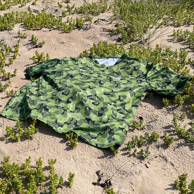 A Training T-Shirt M90 MI lying flat on the beach