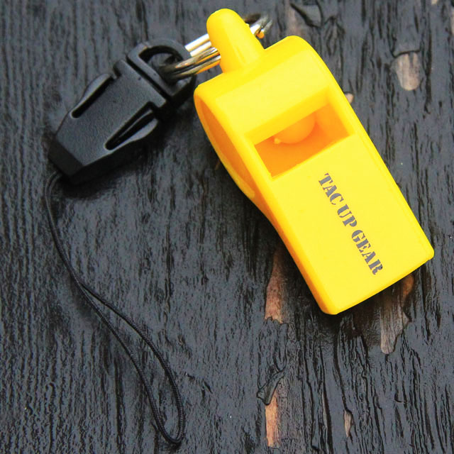 A yellow Whistle H.E.L.P on wooded background.