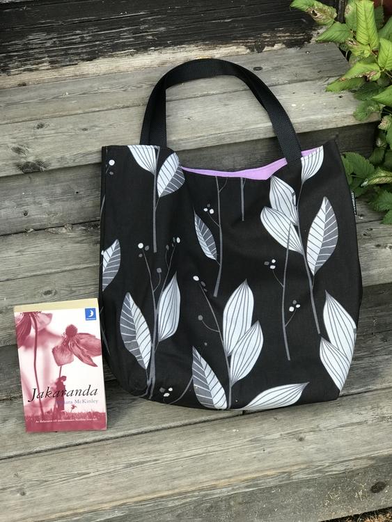 Kasse stor svart gråa löv