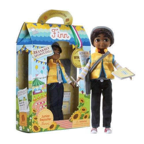Dockan Junior reporter Sammi från varumärket Lottie. Pojkdocka med brun hy, bra representation för mörkhyade barn.