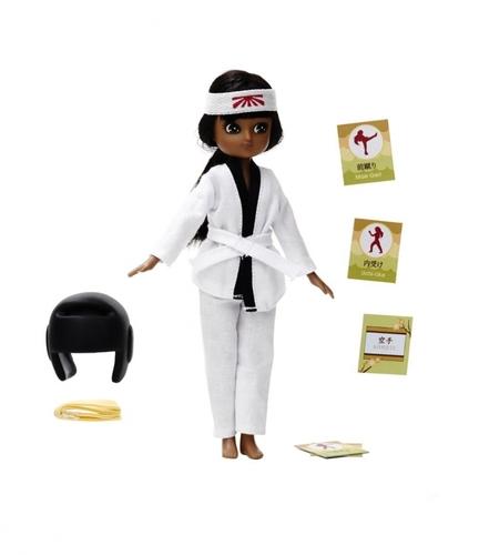 Dockan Kawaii Lottie från varumärket Lottie med Karate-dräkt. Dockan har brun hy och svart hårt, bra representation mörkhyade barn.