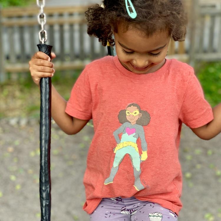 Röd T-shirt ekologisk bomull för barn, med en superhjälte på med mörk hy.