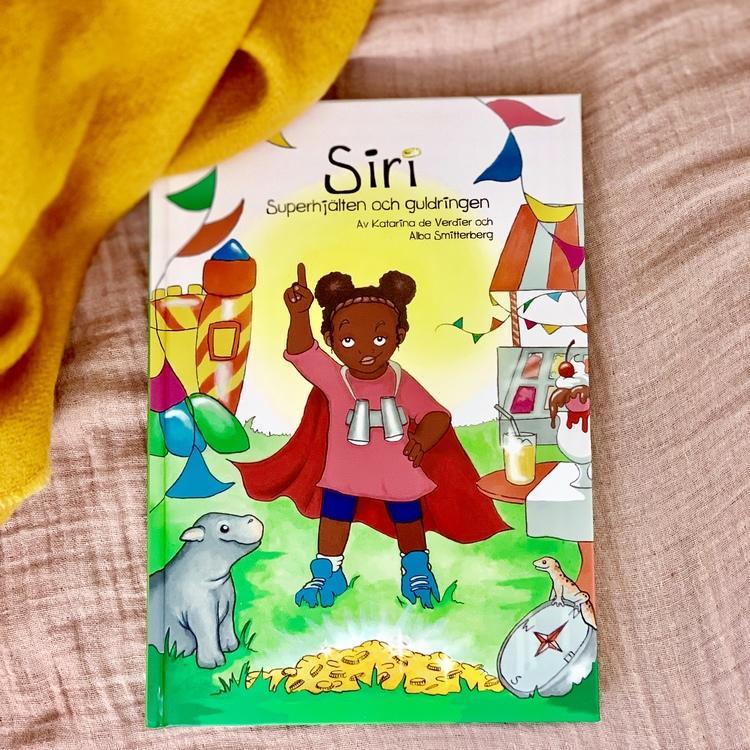Barnbok Siri, Superhjälten och guldringen. Mångfald bland karaktärerna där mörkhyade barn och adopterade barn är representerade. Utspelar sig i Kenya. Författare Katarina de Verdier, Illustratör Alba