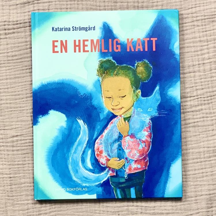 Bilderbok En hemlig katt, författare och illustratör Katarina Strömbård, Hippo förlag. Mångfald bland karaktärerna där barn med mörk hy är representerad, mixat barn och mixad familj.