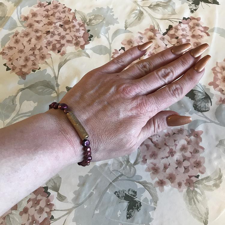 Bronspärla på vinrött pärlarmband