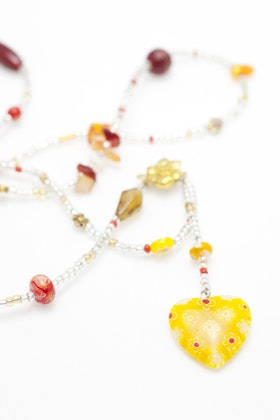 Långt pärlhalsband i gult och rött med millefiorihjärta