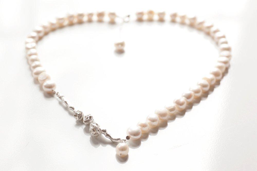 Silverkvist med rosor på vitt pärlhalsband