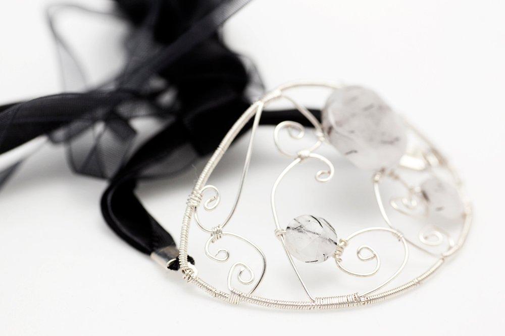 Armband av sten och metalltråd som knytes med tygband