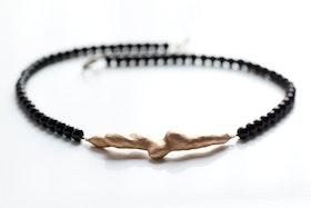 Bronskvist på svart pärlhalsband