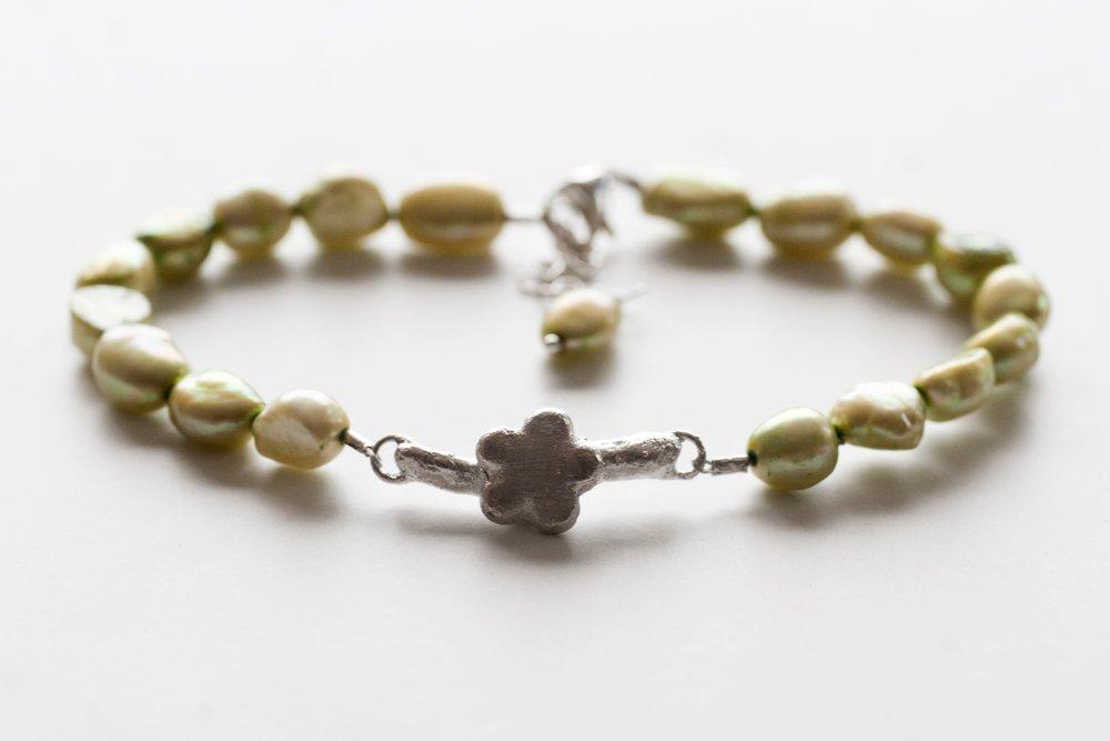 Silverkvist med blomma på grönt pärlarmband