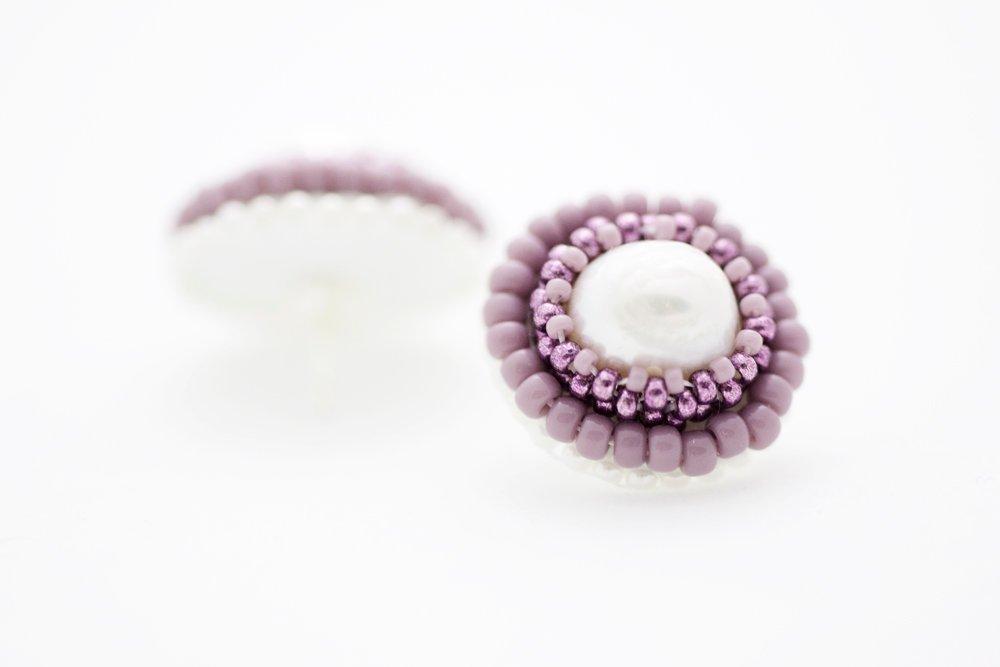 Pärlbroderade örstickare i lila och vitt