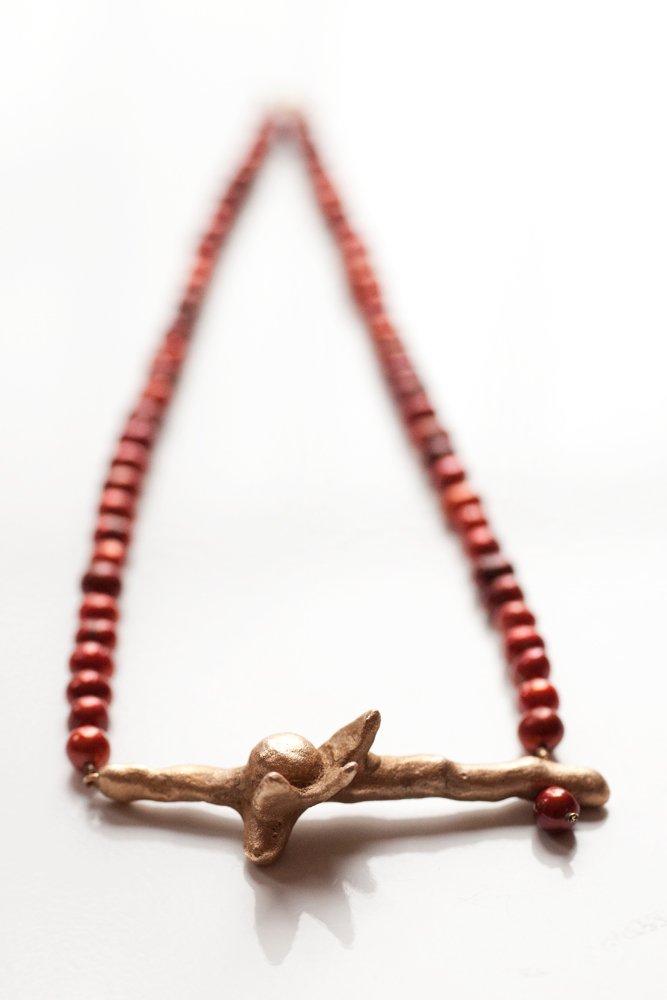 Bronskvist med blomma på rött pärlhalsband