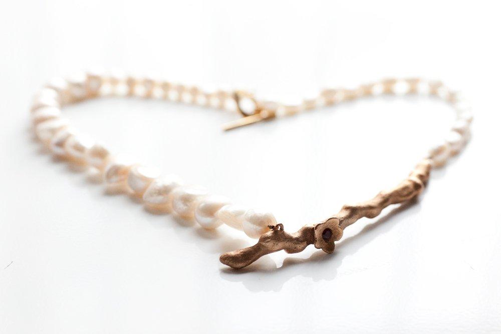 Bronskvist med blommor och kristaller på vitt pärlhalsband