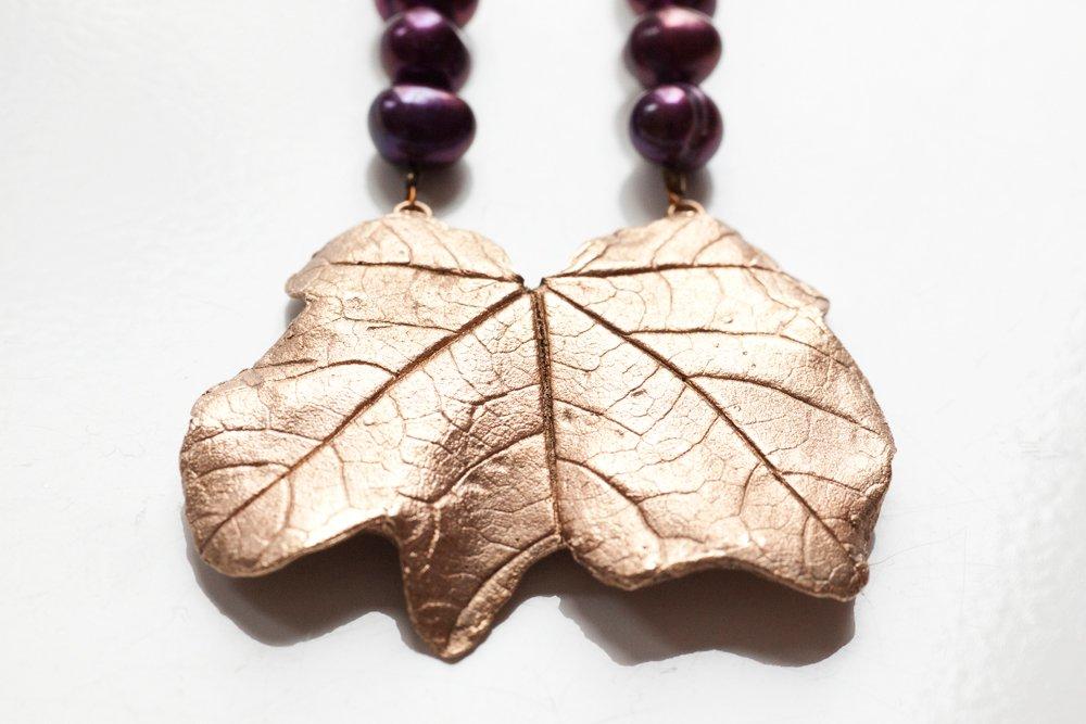 Bronslöv på lila pärlhalsband