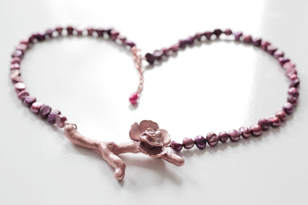 Kopparkvist med blomma på vinrött pärlhalsband