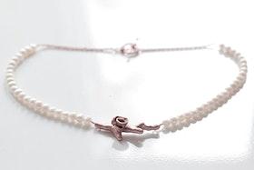Kopparkvist med ros på halsband av vita pärlor och kopparkedja