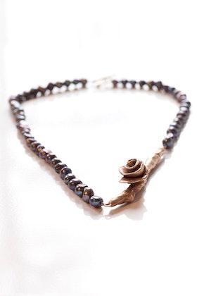 Bronskvist med ros på svart pärlhalsband