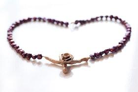 Bronskvist med ros på vinrött pärlhalsband