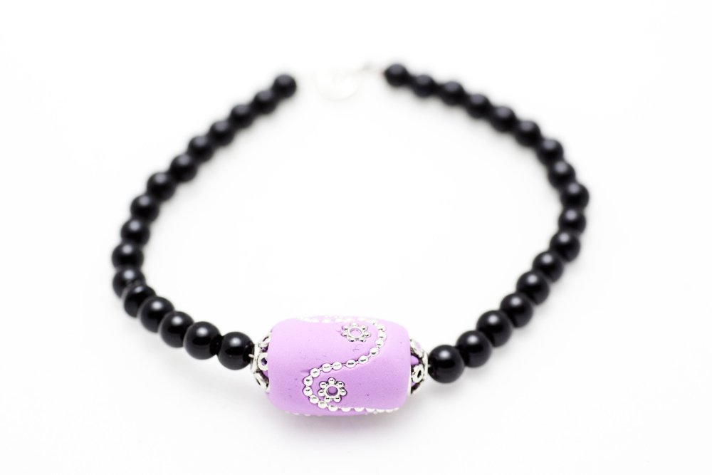 Handgjord pärla i lila och silver på svart pärlarmband