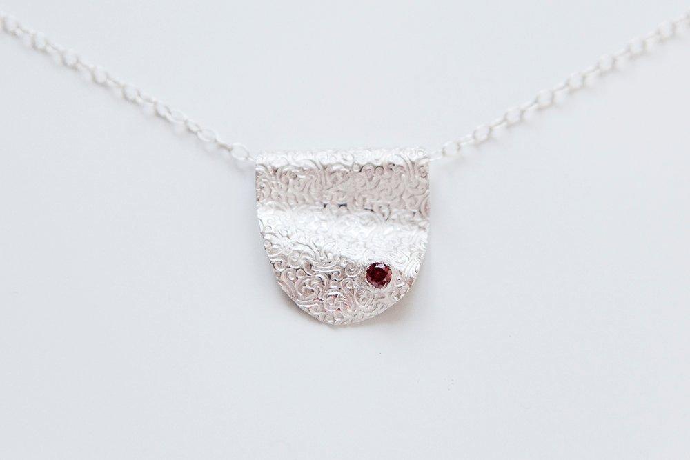 Silverhänge med röd kristall på kedja