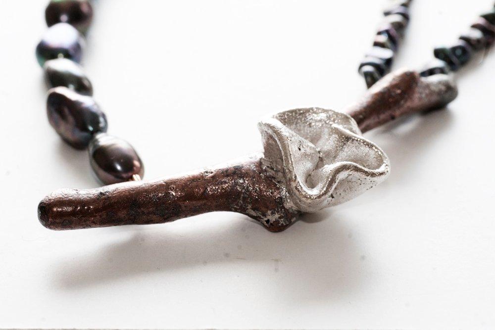Kopparkvist med silverblomma på svart pärlhalsband