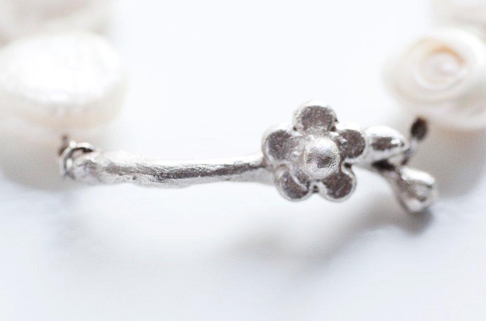 Silverkvist med blomma på vitt pärlarmband