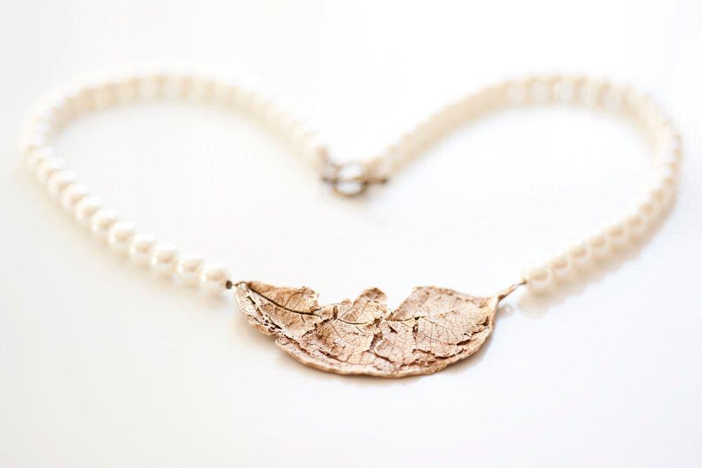 Bronslöv på vitt pärlhalsband