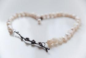 Oxiderad silverkvist med blommor på vitt pärlhalsband