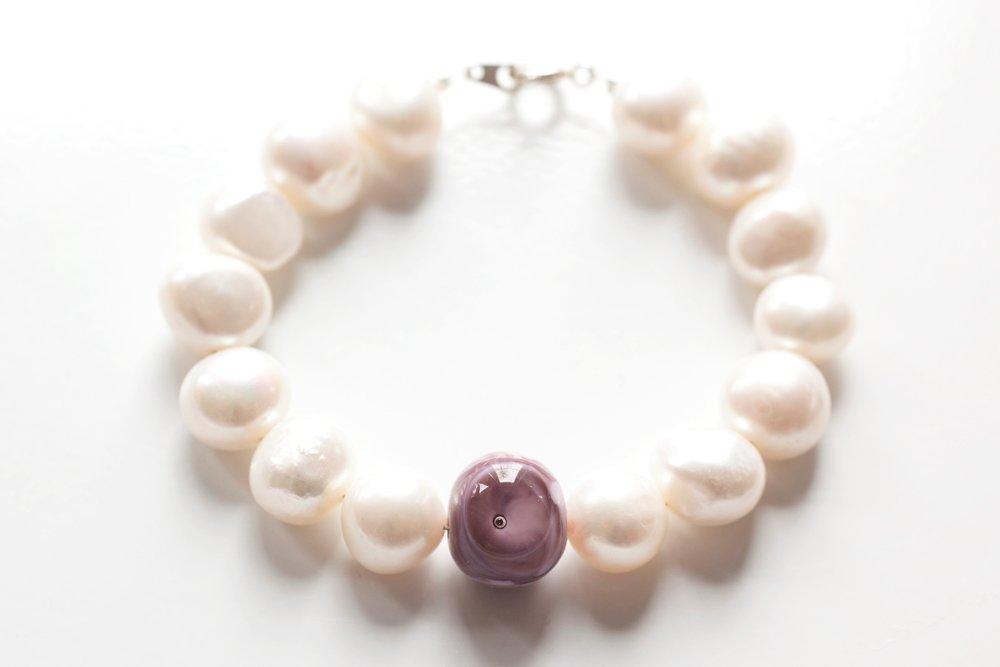 Handgjord lila glaspärla på vitt pärlarmband