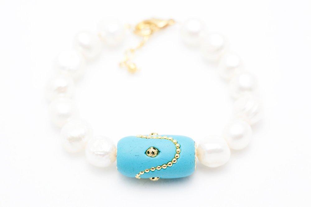 Handgjord pärla i turkos och guld på vitt pärlarmband