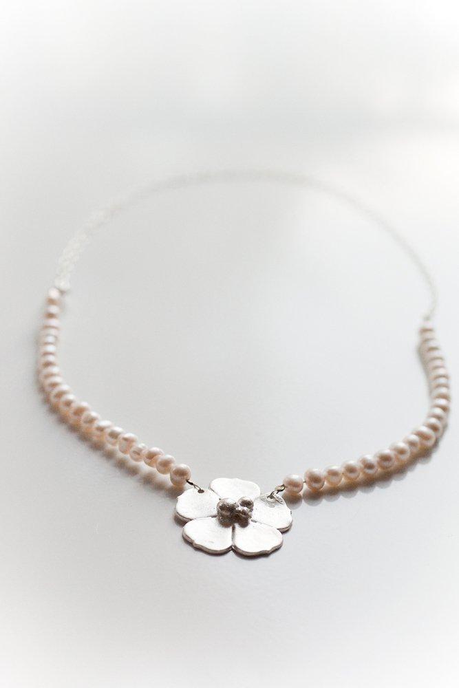 Silverblomma på halsband av pärlor och kedja