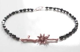 Kopparkvist med blomma på halsband av svarta pärlor