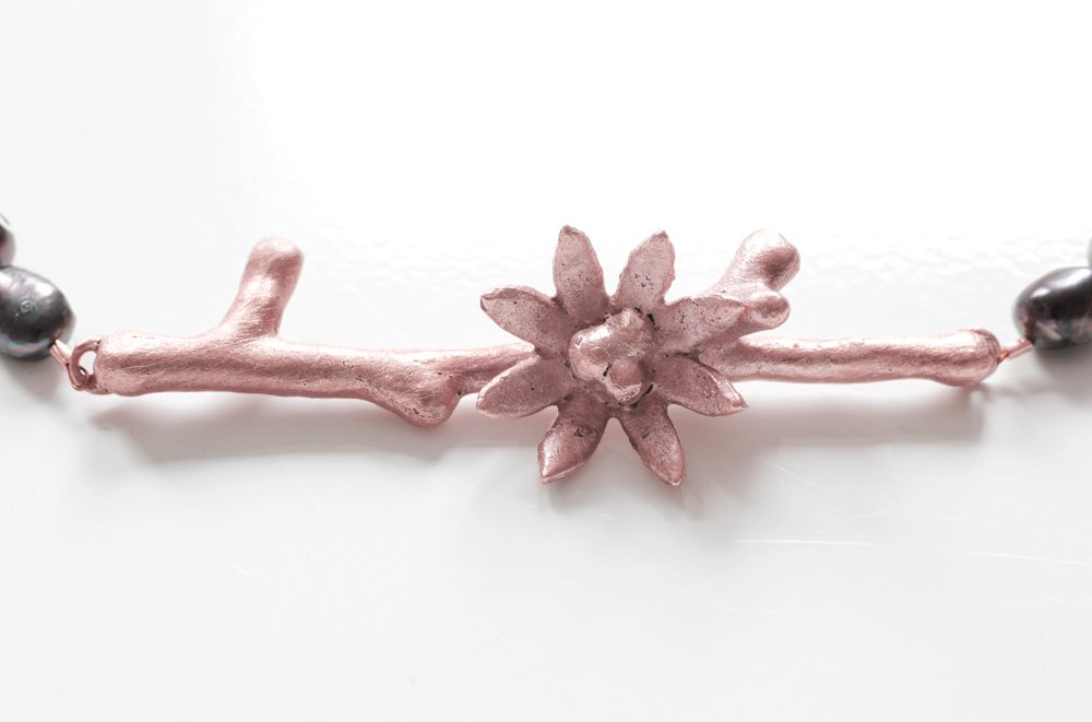 Kopparkvist med blomma på svart pärlhalsband
