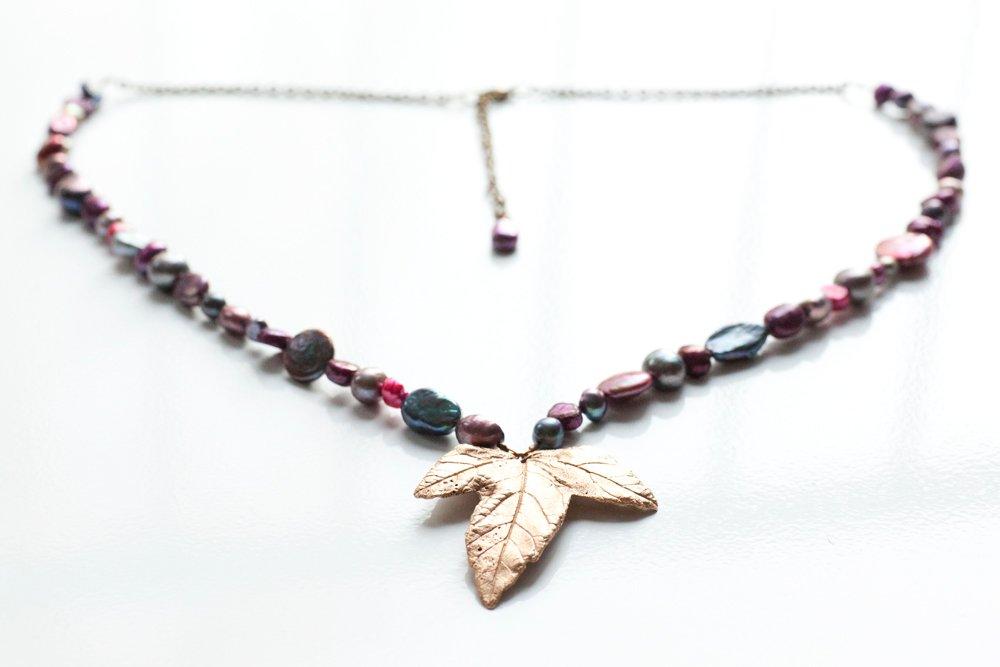 Bronslöv på halsband av pärlor och kedja