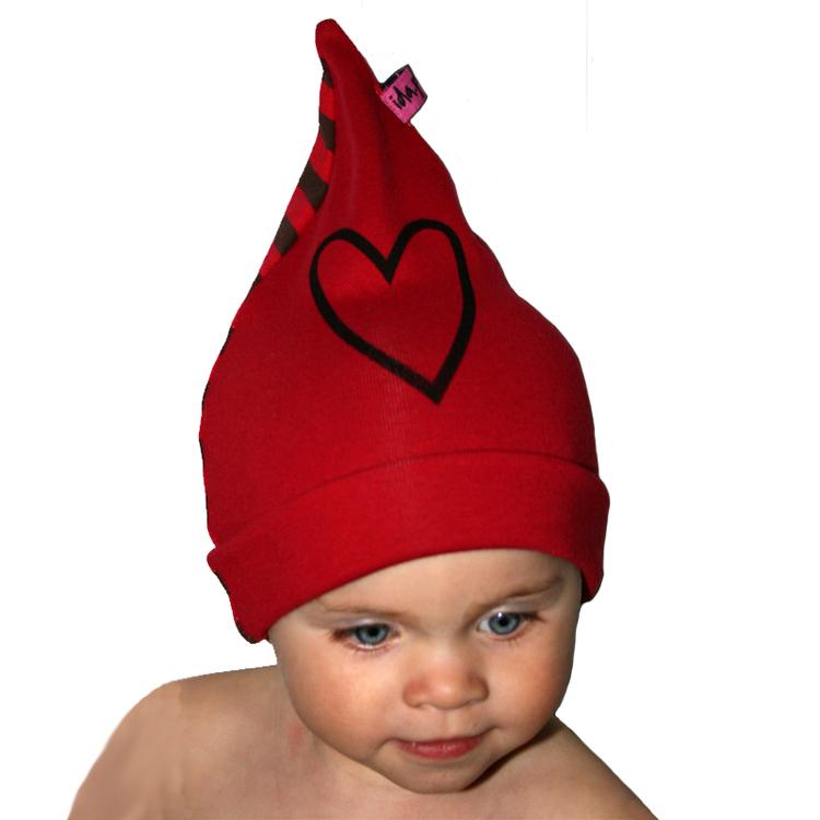 Ett barn med en röd mössa med ett handtryckt hjärta på.