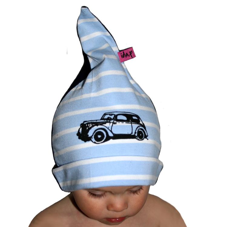Ett barn med en blå och vitrandig mössa på. Med en bil Morris tryckt på