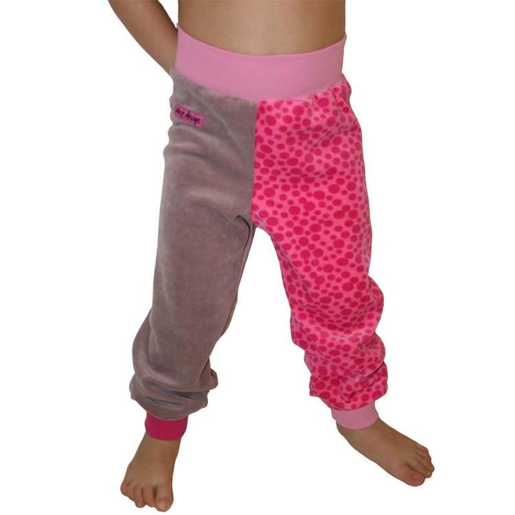 Barn i byxor med rosa prickar. Dimmrosa byxor