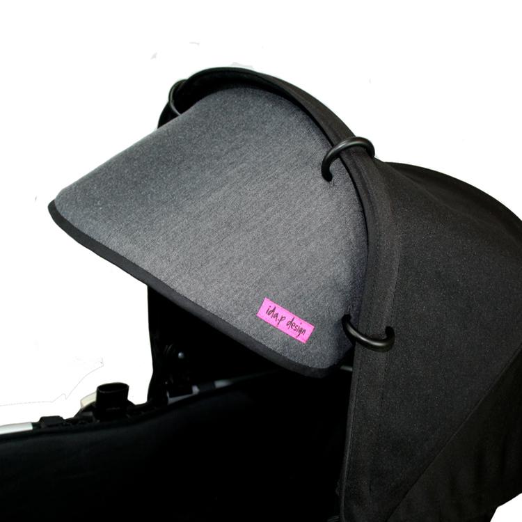 Grå solskärm till barnvagn. Svart kantband och svart baksida. Barnvagnsringar ingår.
