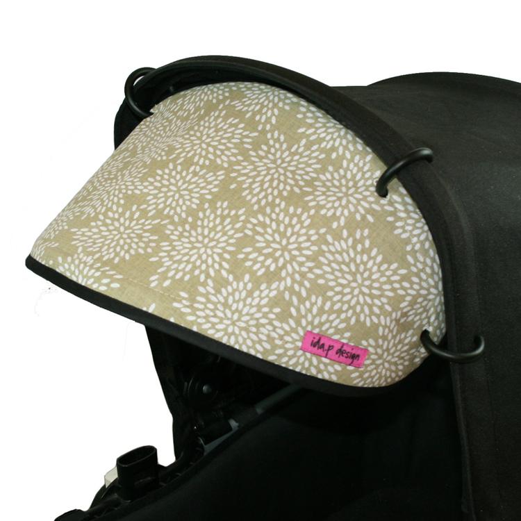 Solskärm till barnvagn som är sytt av ett småbladigt tyg i grönbeige