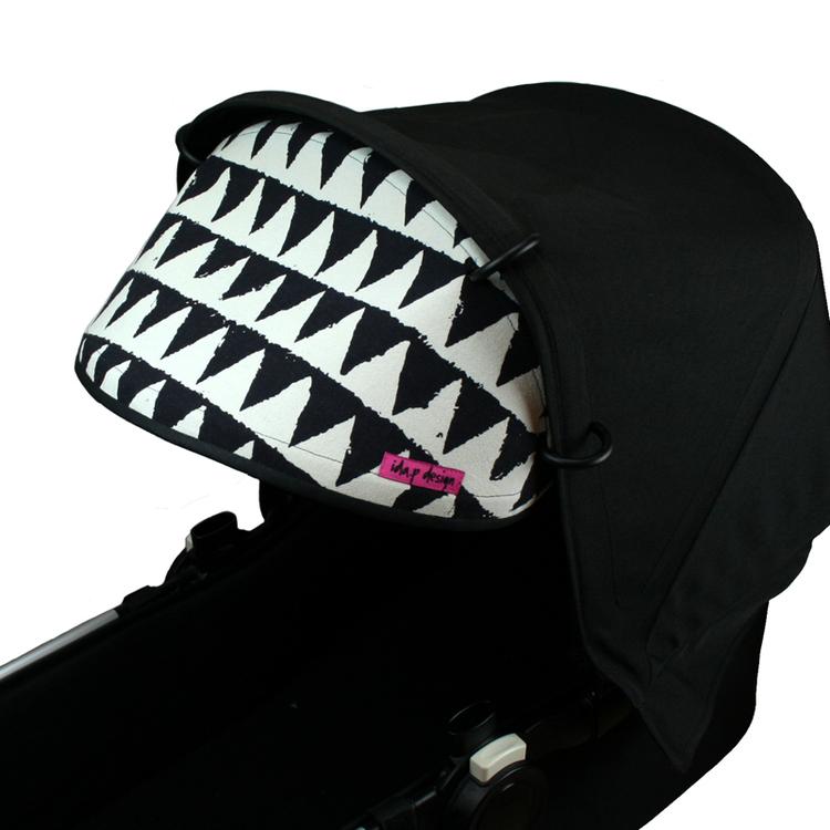 Solskydd till barnvagn i svart och vitt mönstrat tyg med trianglar.