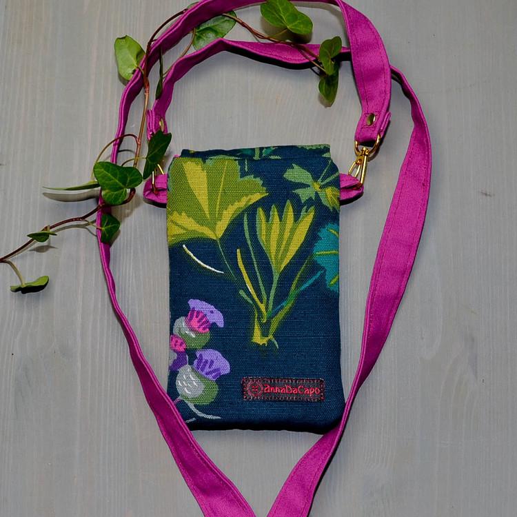 Mobilväska liten med blad, blå blommor och företagsmärkning AnnaDacapo på baksidan.Bärrem i cerise.